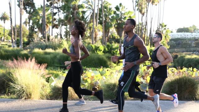 vidéos et rushes de sports d'équipe en cours d'exécution dans la ville. groupe de personnes se mettre en forme - jogging