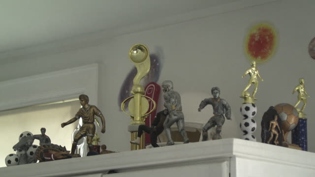 CU Sports trophies on shelf in boy's room, Scarborough, New York, USA