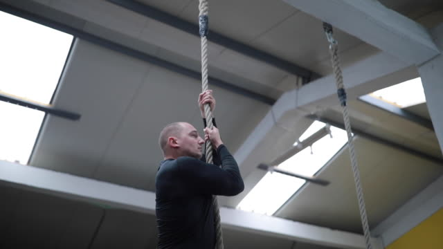 sportsman climbing up gymnastic rope and returning upside down - afferrare video stock e b–roll