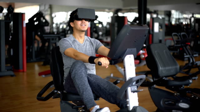 sportsman exercising on stationary bike with virtual reality headset - cyberspace stock videos & royalty-free footage