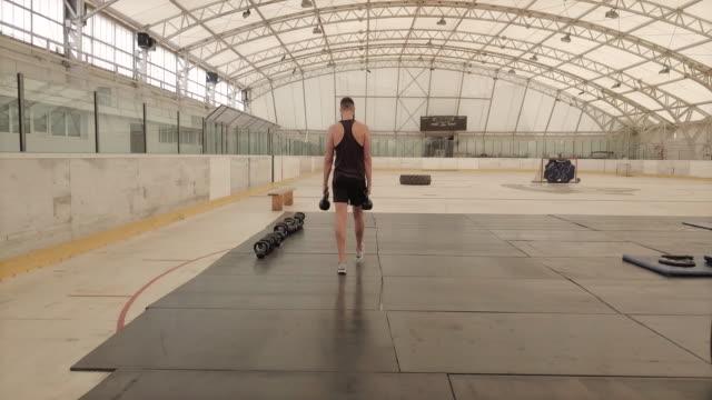vídeos de stock e filmes b-roll de sportsman leaves kettlebells after exercise, panning shot - one mid adult man only