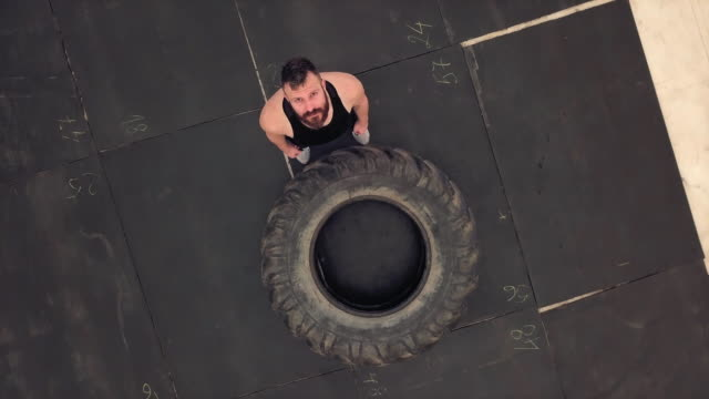 Sportsman preparing for training with tractor tire, aerial view