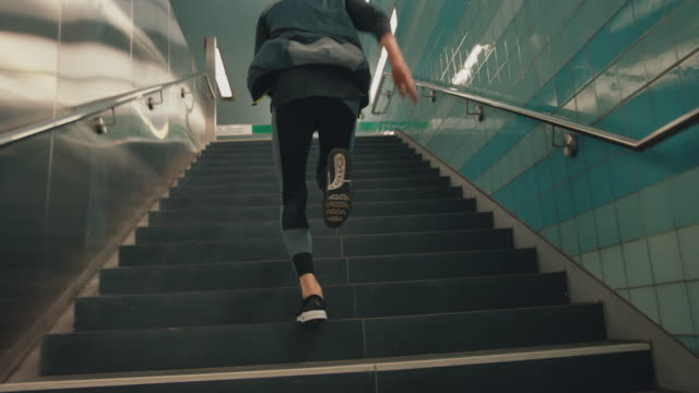 sportsman running up on staircase at subway - moving up stock videos & royalty-free footage