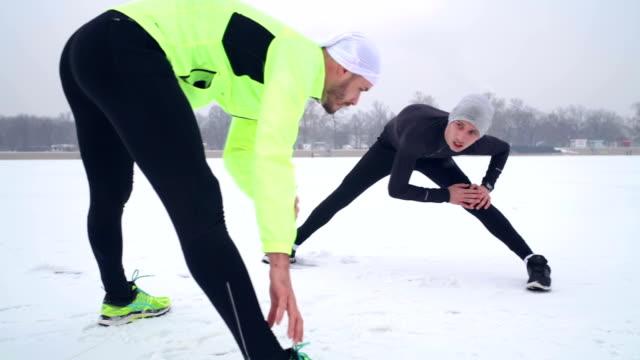 sportsmen stretching bodies on frozen lake - stretching stock videos & royalty-free footage