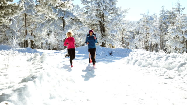 sportspeople running in nature on snowy path - running shorts stock videos and b-roll footage
