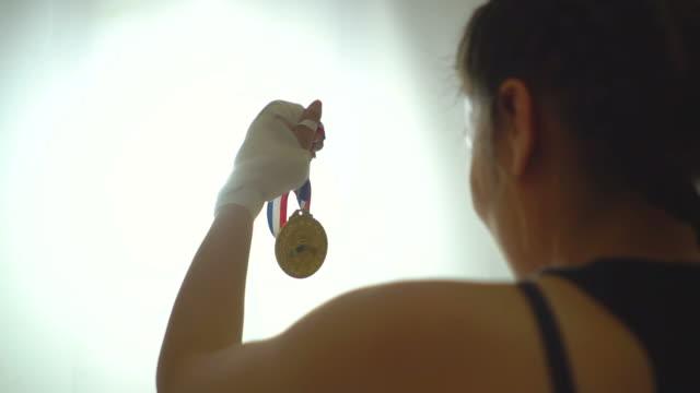 金メダルで彼女の勝利を祝うスポーツウーマン - オリンピック大会点の映像素材/bロール