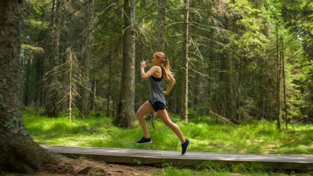 Sportswoman doing cardio workout, running outdoors in nature