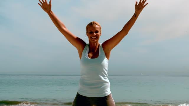 sportswoman doing jumping jacks on the beach - hampelmannsprung stock-videos und b-roll-filmmaterial