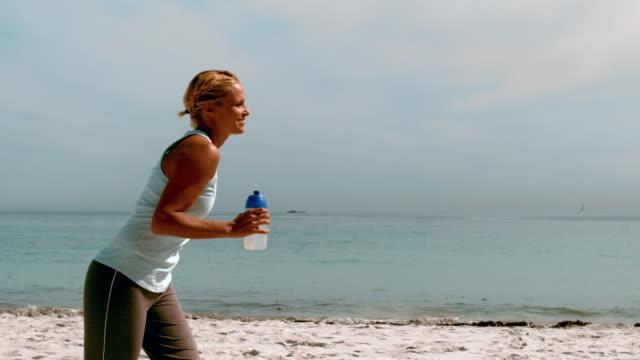 vídeos y material grabado en eventos de stock de sportswoman jogging on the beach - corredora de footing