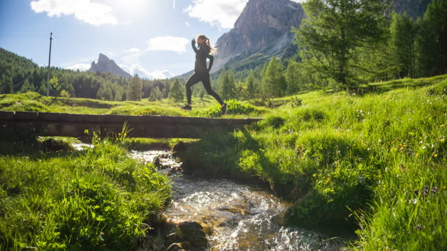 Sportlerin Joggen draußen in der Natur auf einem Pfad in die grüne Landschaft am Wasser