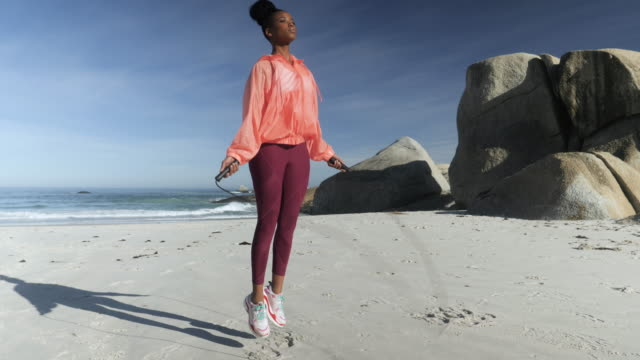 sportswoman jumps rope on beach, medium shot - leggings stock videos & royalty-free footage