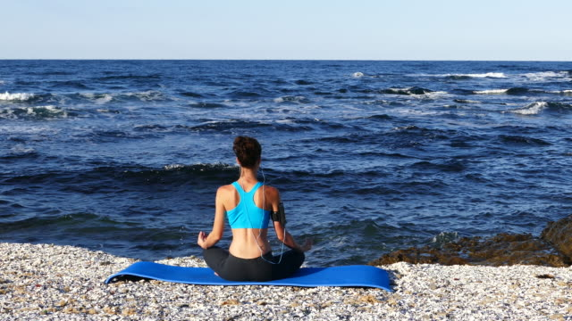 4K Sportswoman practicing yoga on beach