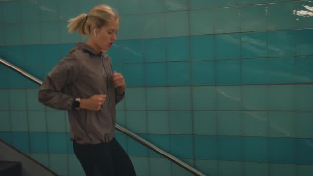 sportswoman kör ner på trappan vid tunnelbanan - ta en paus bildbanksvideor och videomaterial från bakom kulisserna