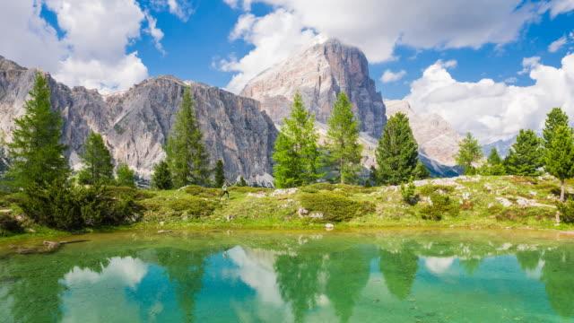 Sportlerin im freien laufen in der Natur auf einem Pfad in einer grünen Landschaft neben Wasser, Berge im Hintergrund