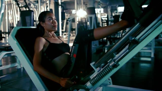 vídeos y material grabado en eventos de stock de deportista, ejercitándose en la máquina de la prensa de pierna - press de banca