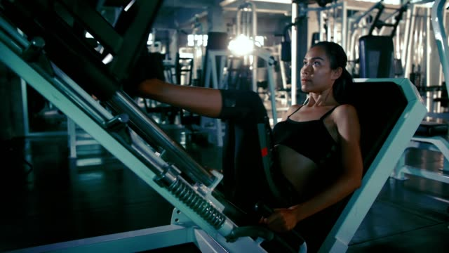 sportswoman working out on leg press machine - cross trainer stock videos and b-roll footage