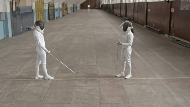 Sportswomen fencing with foils