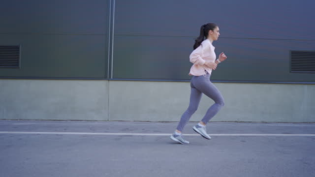 sporty and gorgeous woman exercising outside - side view stock videos & royalty-free footage