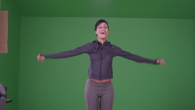 stockvideo's en b-roll-footage met sporty black woman celebrating success on green screen - strekken