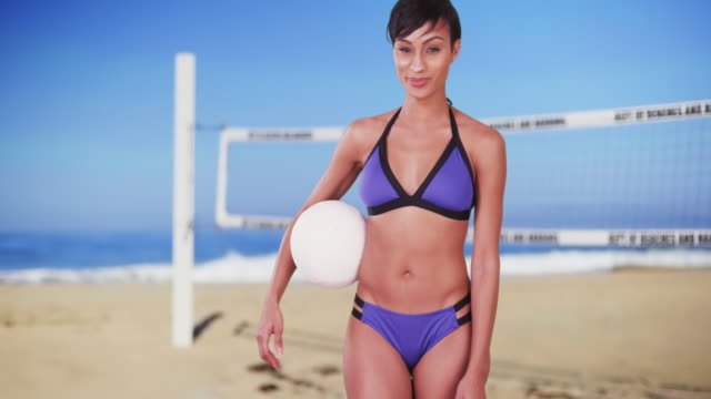 Sporty confident black woman with volleyball on beach in front of net