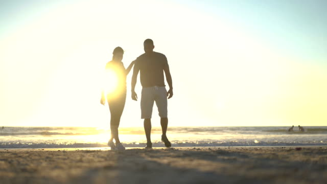 Sporty couple talking at beach during sunset