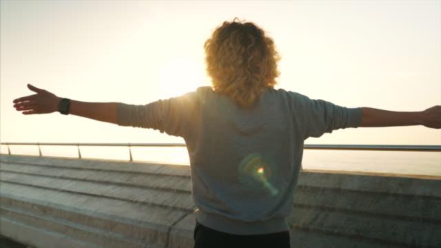 vídeos de stock e filmes b-roll de sporty female enjoying life and beautiful sunshine. - frente ao mar