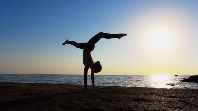 vídeos de stock e filmes b-roll de sporty flexible teen girl doing cartwheel upside down by the sea against the sun. early morning acrobatic training in nature, healthy lifestyle - flexibilidade