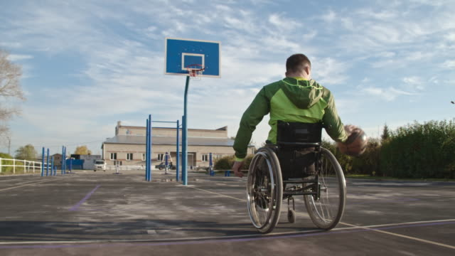 sporty handicapped man shooting hoops on basketball court - wheelchair stock videos and b-roll footage