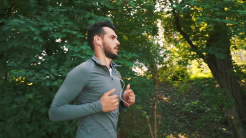 sporty man doing his daily running session. - public park stock videos & royalty-free footage