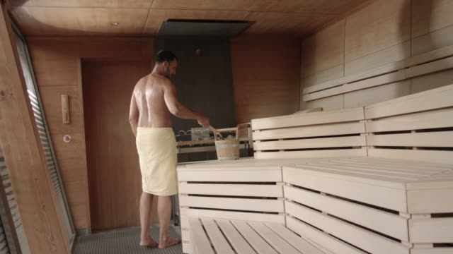 sporty man in his 30s with short dark hair and tanned skin wearing a towel only does a infusion on the sauna stove in a modern design very hot wooden sauna, sitting on the wood bench, doing infusion, enjoying the heat and moment, purging and sweating - sauna stock videos & royalty-free footage