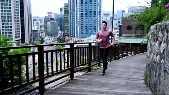 sporty man running in the city - korean ethnicity stock videos & royalty-free footage