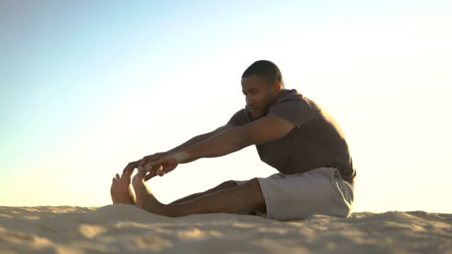 Sporty man touching toes on beach against sky