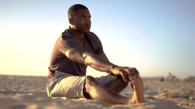 stockvideo's en b-roll-footage met sporty man touching toes on beach against sky - benen gespreid