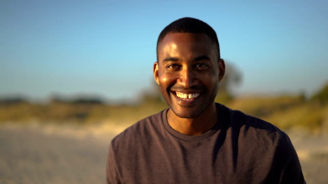 Sporty mid adult man smiling at beach