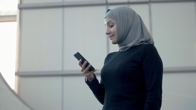 sporty muslim fitness woman in hijab using smart phone (slow motion) - hijab stock videos & royalty-free footage