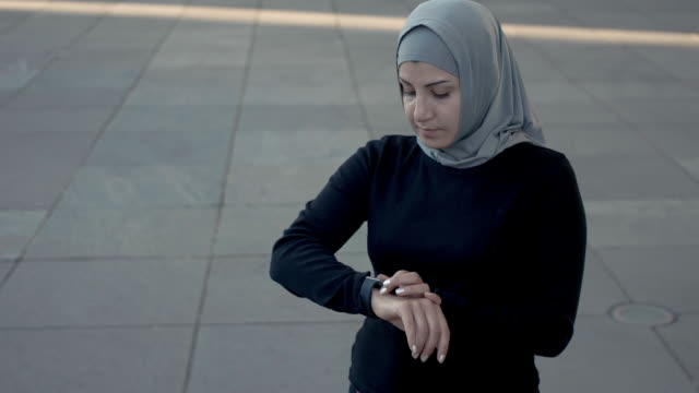 sporty muslim fitness woman in hijab using smart watch (slow motion) - hijab stock videos and b-roll footage