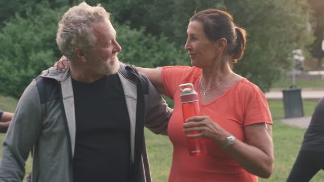 Sporty senior couple talking while walking arm around in park