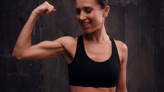 sporty sportswoman flexing biceps isolated over black background - bicep stock videos and b-roll footage