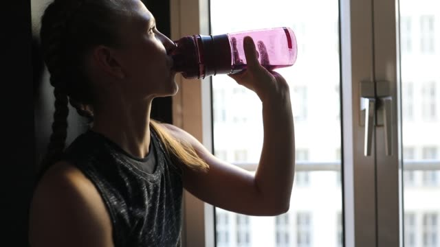sporty woman drinking water by window in gym - water bottle stock videos and b-roll footage