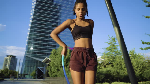 sporty woman exercising with hula hoop in city - shorts stock videos & royalty-free footage