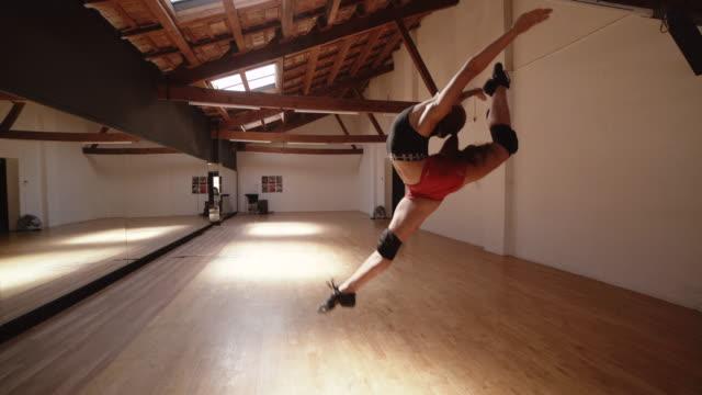 vídeos y material grabado en eventos de stock de sporty woman performing jump at ballet dance floor - motivación