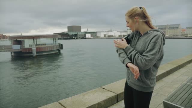 stockvideo's en b-roll-footage met sportieve vrouw uitgevoerd in de stad - shirt met capuchon