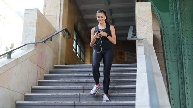 Sporty woman using smart phone on steps
