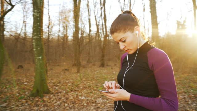 vidéos et rushes de femme sportive à l'aide de téléphone intelligent. - tape measure