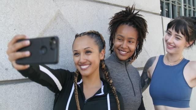 sporty women standing together taking selfie - appoggiarsi video stock e b–roll