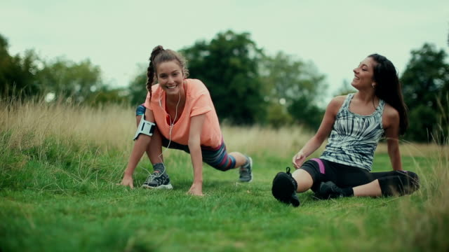 Sporty women stretching muscles and talking