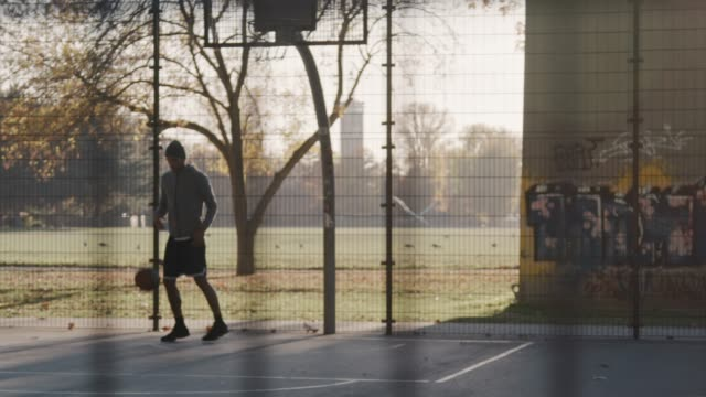 sporty young man throwing basketball in hoop - recinzione video stock e b–roll