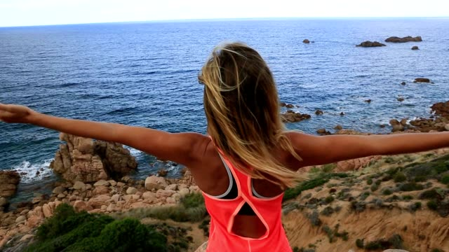 sporty young woman arms outstretched by the sea - sassari stock videos & royalty-free footage