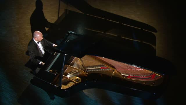 vidéos et rushes de grue haute définition: éclairage studio pianiste jouant du piano - grand lit