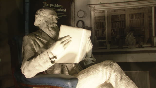 a spotlight illuminate a statue of charles darwin in the natural history museum in london. - marble stock videos & royalty-free footage